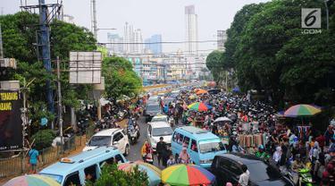 Sejumlah mobil terjebak kemacetan di kawasan Tanah Abang, Jakarta, Minggu (26/5/2019). Banyaknya masyarakat yang berbelanja di pasar tanah abang membuat arus lalu lintas di kawasan tersebut padat. (Liputan6.com/Angga Yuniar)