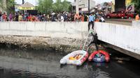 Warga melihat petugas melakukan pencarian buaya di Kali Grogol, Jakarta Barat, Jumat (29/6). Pencarian buaya sempat membuahkan hasil pada hari ketiga pencarian, namun kondisi teknis lapangan membuat predator itu kembali lepas. (Liputan6.com/Arya Manggala)