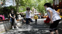 Anak-anak dengan mengenakan masker bermain di taman umum Kugulu, di Ankara, Rabu (13/5/2020). Turki mengizinkan anak-anak berusia 14 tahun ke bawah untuk meninggalkan rumah pertama kalinya dalam 40 hari sebagai bagian dari rencana normalisasi COVID-19 di negara tersebut. (AP/Burhan Ozbilici)