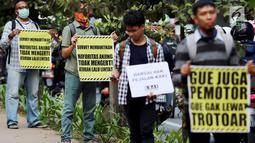 Sejumlah aktivis Koalisi Pejalan Kaki melakukan aksi peduli pejalan kaki di kawasan pedestrian Kasablanka, Jakarta, Kamis (22/8). Mereka menyerukan agar tidak menggunakan trotoar sebagai tempat parkir dan berjualan.(Liputan6.com/JohanTallo)