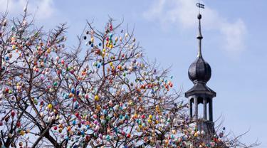 Sebuah pohon robinia yang dihias dengan 10.000 telur paskah warna-warni di kota Saalfeld, Jerman, Jumat (30/3). Pohon Paskah, merupakan tradisi lain yang berumur berabad-abad dan dibuat dari pohon atau semak kecil yang masih hidup. (AP/Jens Meyer)