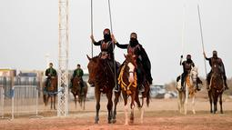 Perempuan Arab menunggangi kuda selama Festival Souk Okaz 2019 di Kota Taif, Arab Saudi, Rabu (7/8/2019). Perempuan penunggang kuda dari berbagai negara Arab ambil bagian dalam Festival Souq Okaz 2019. (AMER HILABI/AFP)