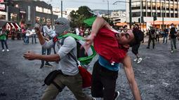 Aksi melempar batu para demonstran ke kedutaan Israel di Athena, Yunani, Selasa (15/5). Mereka mengecam tindakan tentara Israel menembak mati puluhan warga Palestina di perbatasan Gaza yang berunjuk rasa menentang pembukaan kedubes AS (AFP/Aris MESSINIS)