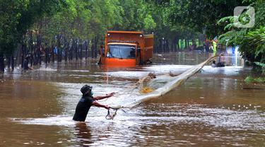 FOTO: Warga Jala Ikan di Tengah Jalan yang Terendam Banjir
