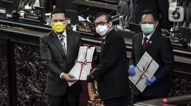 Ketua Komisi II Ahmad Doli Kurnia (kiri) memberikan salinan Perppu kepada Menkumham Yasonna Laoly dan Mendagri Tito Karnavian usai Rapat Paripurna ke-18 Masa Persidangan IV 2019-2020 di Kompleks Parlemen, Jakarta, Selasa (14/7/2020). Perppu Pilkada disahkan menjadi UU. (Liputan6.com/Johan Tallo)