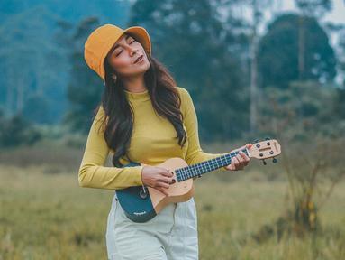 Beberapa momen, Dinda Kirana memang terlihat begitu senang memainkan alat musik ukulele. Dengan gaya santainya di alam bebas, Dinda sangat menikmati momen-momen bersenandung dengan ukulelenya. (Liputan6.com/IG/@dindakirana.s)