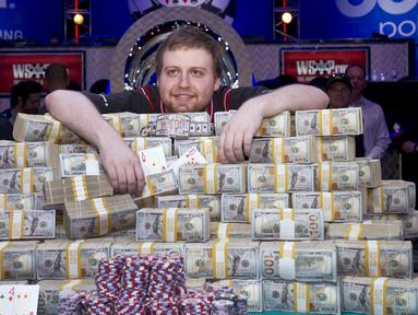 Joe McKeehen berpose diatas tumpukan uang yang ia menangkan dalama kejuaraan poker dunia di Las Vegas, Amerika Serikat, (10/11/2015). McKeehen memenangkan uang 107 Miliar rupiah dan gelang tanda kemenangan dalam kejuaraan ini. (REUTERS/Steve Marcus)