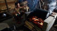 Seorang pria memanggang biji kopi robusta menggunakan alat tradisional di salah satu industri rumah tangga di Ulee Kareng, Aceh, Rabu (20/11/2019). Kopi yang diolah secara tradisional itu dijual dengan kisaran harga beragam tergantung kualitas. (CHAIDEER MAHYUDDIN/AFP)