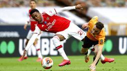 Pemain Arsenal, Joe Willock, berebut bola dengan pemain Wolverhampton Wanderers, Diogo Jota, pada laga Premier League di Stadion Molineux, Sabtu (4/6/2020). Arsenal menang dengan skor 2-0. (AP/Michael Steele)