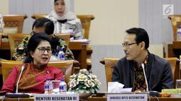 Menteri Kesehatan Nila Moeloek berbincang dengan Direksi PBJS Kesehatan, Fahmi Idris di sela rapat kerja dengan Komisi IX DPR di Kompleks Parlemen MPR/DPR-DPD, Senayan, Jakarta, Kamis (29/3). (Liputan6.com/JohanTallo)