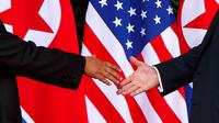 Presiden Amerika Serikat (AS) Donald Trump menggapai tangan Pemimpin Korea Utara, Kim Jong-un untuk bersalaman dalam pertemuan bersejarah di resor Capella, Pulau Sentosa, Singapura, Selasa (12/6). (AP Photo / Evan Vucci)