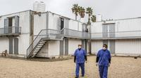 Petugas kesehatan yang mengenakan masker berjalan di zona karantina perbatasan Rafah dengan Mesir di Jalur Gaza, Palestina, Minggu (16/2/2020). Kementerian Kesehatan Palestina membangun zona karantina sebagai upaya untuk mengantisipasi wabah virus corona atau COVID-19. (SAID KHATIB/AFP)