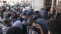 Antrean orang-orang untuk memasuki toko Niketown di London, Senin (15/6/2020). Antrean panjang terjadi di luar toko-toko yang berada di sejumlah kota di Inggris saat negara itu melakukan pelonggaran lockdown dan mulai membuka pusat perbelanjaan. (AP/Matt Dunham)
