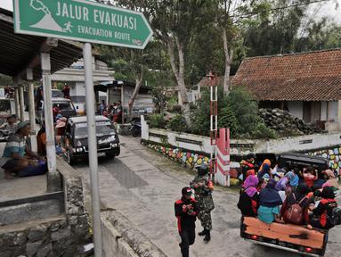 Penduduk desa menggunakan mobil bak terbuka dievakuasi dari rumah mereka di lereng Gunung Merapi, di Krinjing, Jawa Tengah, Jumat (6/11/2020). Evakuasi dilakukan bagi warga lereng Merapi menyusul peningkatan status aktivitas vulkanik gunung tersebut. (AP Photo/Taufiq Rozzaq)