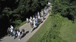 Rakyat Bosnia berjalan melalui daerah pegunungan dekat Crni Vrh saat memperingati 25 tahun pembantaian Srebrenica di Bosnia, Rabu (8/7/2020). Acara tersebut untuk mengenang lebih dari 8.000 orang yang tewas selama 10 hari pembantaian setelah Srebrenica diserbu pasukan Serbia. (AP Photo/Kemal Softic)