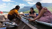 Nelayan perempuan membersihkan ikan di atas perahu di Danau Nam Ngum di Provinsi Vientiane, Laos, pada 15 Desember 2020. Terletak di hilir Sungai Nam Ngum dan sekitar 80 km dari ibu kota, Danau Nam Ngum merupakan tempat dengan ratusan pulau kecil yang tersebar di dalamnya. (Xinhua/Kaikeo Saiyasane)