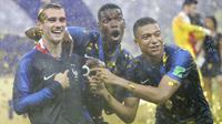 Pemain Prancis, Antoine Griezmann, Paul Pogba dan Kylian Mbappe, melakukan selebrasi usai menjuarai Piala Dunia dengan di Stadion Luzhniki, Moskow, Minggu (15/7/2018). Prancis menang 4-2 atas Kroasia. (AP/Matthias Schrader)