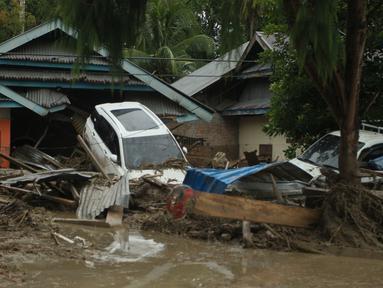 Kendaraan hanyut oleh banjir bandang di sebelah rumah-rumah di desa Radda di Kabupaten Luwu Utara, Sulawesi Selatan (14/7/2020). Hujan lebat yang mengakibatkan tiga sungai meluap telah menyapu rumah-rumah, kendaraan dan berbagai fasilitas umum di enam kecamatan di Kabupaten Luwu Utara. (AFP/Aryanto)