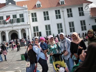 Pengunjung foto bersama di depan Museum Sejarah Kota Tua, Jakarta, Kamis (27/12). Kawasan wisata Kota Tua dipadati wisatawan dari dalam kota maupun luar kota Jakarta selama libur sekolah. (Liputan6.com/Faizal Fanani)