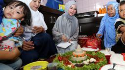 Artis Chacha Frederica mencoba nasi tumpeng saat menjadi juri lomba masak di Rumah Amalia, Cildeug, Kota Tangerang, Minggu (9/9). Kegiatan bersama warga sekitar dan anak yatim piatu mengusung tema Meraih Mimpi. (Liputan6.com/Fery Pradolo)