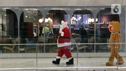 """Petugas yang mengenakan kostum Sinterklas berkeliling saat menghibur pengunjung di Senayan City Mall, Jakarta, Jumat (25/12/2020). Pengunjung bisa berswafoto dan menikmati momen Natal bersama keluarga dan orang terkasih dengan """"Santa and Friend"""". (Liputan6.com/Herman Zakharia)"""
