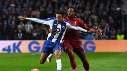 Penyerang Liverpool, Dovick Origi berduel dengan Eder Militao pada leg kedua babak perempat final Liga Champions yang berlangsung di Stadion do Dragao, Porto, Kamis (17/4). Liverpool menang 4-1 atas Porto. (AFP/Miguel Riopa)