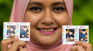 Pekerja pos Nurshafiqa Kasim berpose dengan prangko bergambar PM Malaysia Mahathir Mohamad di sebuah kantor pos di Kuala Lumpur, Selasa (10/7). Prangko bergambar Mahathir ini untuk merayakan ulang tahunnya yang ke-93. (Mohd RASFAN/AFP)