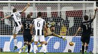 Kiper AC Milan, Gianluigi Donnarumma, berjibaku saat menghalau bola pemain Juventus pada laga pekan ke-9 Serie A 2016-2017, di San Siro, Minggu (23/10/2016) dini hari WIB. Ma. (AFP/Marco Bertorello)