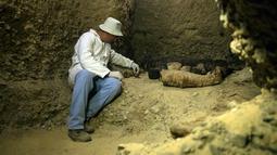 Arkeolog memeriksa mumi terbungkus kain linen di ruang pemakaman di Provinsi Minya, Mesir, Sabtu (2/2). Mumi tersebut diperkirakan berasal dari era Ptolemaic. (AP Photo/Roger Anis)