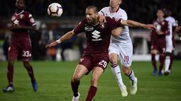 Duel antara De Silvesri dan Piatek pada laga lanjutan Serie A yang berlangsung di Stadion Turin, Torino, Senin (30/4). AC Milan kalah 0-2 kontra Torino. (AFP/Marco Bertorello)