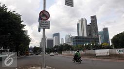 Pengendara motor melintasi jalan Sudirman, Sabtu, (30/4). Ditlantas Polda Metro akan menunggu pengadaan 600 bus terealisasi baru memberlakukan pelarangan sepeda motor dari kawasan Senayan hingga Thamrin. (Liputan6.com/Johan Tallo)