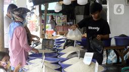 Pedagang beras melayani pembeli di pinggir Jalan Raya Pamulang, Tangerang Selatan, Banten, Jumat (11/12/2020). Jelang Natal dan Tahun Baru 2021, harga beras dipasaran masih normal tidak ada kenaikan. (merdeka.com/Dwi Narwoko)