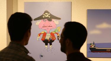 """Pengunjung melihat karikatur di pameran kartun """"Pirates of the Queen"""" yang menampilkan karya seni  seniman Iran yang menggambarkan Ratu Elizabeth II Inggris sebagai """"bajak laut"""" atas penyitaan tanker minyak Iran di Pusat Seni dan Budaya Osveh di ibukota Teheran (30/7/2019). (AFP Photo/Atta Kenare)"""