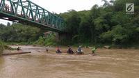 Sebuah rakit mengangkut motor dan warga menyeberangi Sungai Cisadane di Rumpin, Bogor, Selasa (13/3). Mereka terpaksa menaiki rakit akibat jembatan yang merupakan akses jalan utama Ciseeng -Rumpin masih dalam perbaikan. (Liputan6.com/Achmad Sudarno)