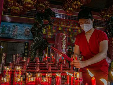 Warga keturunan Tionghoa menyalakan lilin saat sembahyang di Vihara Amurva Bhumi, Jakarta, Kamis (11/2/2021). Sembahyang jelang Imlek ini sebagai ungkapan syukur atas rejeki dan keselamatan dari Tuhan serta untuk pengharapan kehidupan lebih baik di tahun Kerbau Logam. (Liputan6.com/Faizal Fanani)