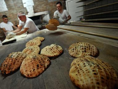 Pekerja membuat somun di sebuah toko roti di kota tua Sarajevo, Bosnia and Herzegovina, Kamis (30/4/2020). Somun merupakan roti tawar tradisional  asal Bosnia yang dibuat sejak abad ke-16 di Sarajevo. (ELVIS BARUKCIC/AFP)