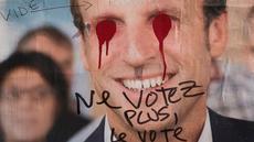 Poster Capres Prancis,  Emmanuel Macron terlihat rusak di Paris, Selasa (2/5). Sejumlah poster capres Prancis lainnya juga tampak rusak yang diduga dilakukan oleh orang yang tidak suka dengan mereka. (AFP PHOTO / JOEL SAGET)
