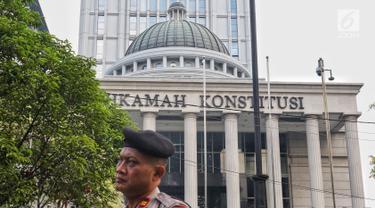 Polisi berjaga menjelang sidang perdana MK Pemilu 2019 di halaman depan Gedung Mahkamah Konstitusi, Jakarta, Jumat, (14/6/2019). Sekitar 30 ribu pesonil gabungan diterjunkan untuk mengawal jalannya sidang. (Liputan6.com/Johan Tallo)
