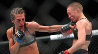 Joanna Jedrzejczyk (kiri) melayangkan pukulan tangan kiri ke wajah lawannya Rose Namajunas pada kejuaraan UFC 223 kelas strawweight di Barclays Center, New York, 7 April 2018. (Ed Mulholland/Getty Images/AFP)