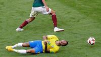 Penyerang timnas Brasil, Neymar mengerang kesakitan di atas lapangan pada babak 16 besar Piala Dunia 2018 melawan Meksiko di Samara Arena, Senin (2/7). Neymar memang menjadi bintang saat Brasil mengalahkan Meksiko 2-0. (AP/Sergei Grits)