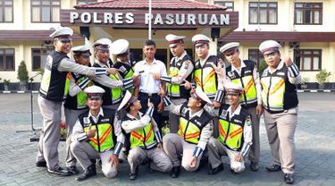 Pria bernama Polisi (Kemeja putih) berpose dengan anggota kepolisian di halaman Polres Pasuruan (21/11). Remaja 22 tahun asal Dusun Pengarengan, Pasuruan, mulai bekerja di Mapolres Pasuruan, Senin (20/11/2017) pagi. (AFP Photo)