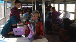 Anak-anak Afghanistan membaca buku dalam bus yang dijadikan perpustakaan keliling di Kabul, 4 April 2018. Bus umum yang telah diubah fungsi dan bentuknya tersebut memberikan kebahagiaan tersendiri bagi anak-anak Afghanistan. (AFP/Shah MARAI)