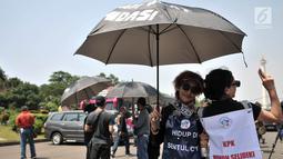 Aksi massa dari Komite Warga Sentul City mengenakan payung hitam di depan Istana Negara, Senin (30/4). Mereka meminta proses hukum terhadap pengembang perumahan Sentul City karena diduga terjadi penguasaan pengelolaan air. (Merdeka.com/Iqbal Nugroho)