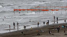 Warga Iran saat bermain di pantai di kota Laut Kaspia, Izadshahr, provinsi Mazandaran utara (8/7/2019). Terdapat lima negara yang membatasi Laut Kaspia. Selain Iran, semuanya adalah bekas negara-negara Uni Soviet. (AFP Photo/Atta Kenare)