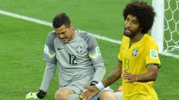 Kiper Brasil, Julio Cesar dan Dante tampak lesu usai ditaklukkan Jerman pada laga semifinal Piala Dunia 2014 di Stadion The Mineirao (8/7/2014). Jerman menang 7-1 atas Brasil. (AFP/Gabriel Bouys)