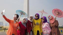 Sejumlah wanita berswafoto mengenakan baju kebaya mengikuti hari Gerakan Nasional kembali ke busana identitas Indonesia di Jakarta, Selasa (2/7/2019). Gerakan ini dinamakan sebagai Selasa Berkebaya untuk mengajak anak-anak muda tetap menjaga kelestarian busana kebaya. (Liputan6.com/Faizal Fanani)