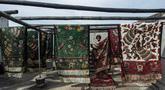 """Seorang pekerja menjemur batik di pabrik """"batik"""" kain tradisional Indonesia di Sidoarjo, Jawa Timur (12/11/2019). UNESCO menetapkan batik sebagai karya agung lisan dan warisan budaya takbenda kemanusiaan. (AFP Photo/Juni Kriswanto)"""