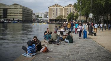 Orang-orang bersantai di Bassin de la Villette Canal, Paris, Prancis, Sabtu (5/6/2021). Jumlah kasus baru COVID-19 di Prancis semakin menurun. (AP Photo/Lewis Joly)