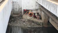 Warga melihat petugas melakukan pencarian buaya di Kali Grogol, Jakarta Barat, Jumat (29/6). Pencarian buaya sempat membuahkan hasil pada hari ketiga, namun kondisi teknis lapangan membuat predator itu kembali lepas. (Liputan6.com/Arya Manggala)