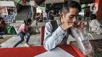 Pemudik meniup kantong saat dites dengan GeNose C19 di Terminal Kampung Rambutan, Jakarta, Minggu (23/5/2021). Pengelola Terminal Kampung Rambutan memberlakukan tes Genose sebagai syarat wajib bagi para pemudik yang baru tiba guna memutus penyebaran virus Covid-19. (merdeka.com/Iqbal S Nugroho)